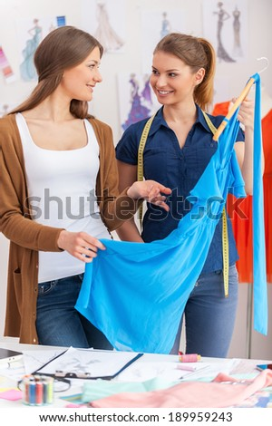 Satisfied with new collection. Two attractive women looking at each other and smiling while holding blue dress - stock photo