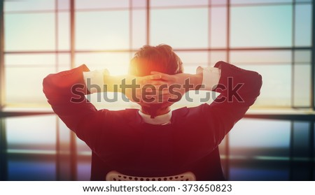 Satisfied with work done. Happy young business man looking out windows in office.  - stock photo