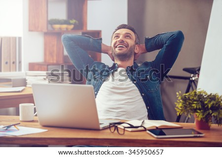 Satisfied with work done. Happy young man working on laptop while sitting at his working place in office - stock photo