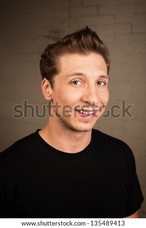 Satisfied young white male adult in black shirt - stock photo