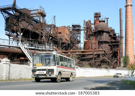 SATKA, RUSSIA - AUGUST 16, 2008: White PAZ 3205 small city bus at the background of the ancient cast iron foundry. - stock photo