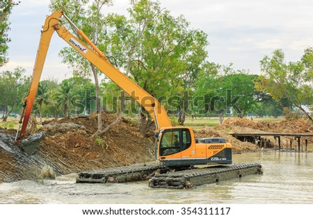 SATTAHIP CHONBURI - DEC,23 : The dirty backhoe working in mud lake for take the mud dam beside the pool site where is renovated new landscape in golf course . THAILAND DEC,23 2015 - stock photo