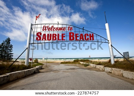 Sauble Beach Sign over roadway entrance red letters - stock photo