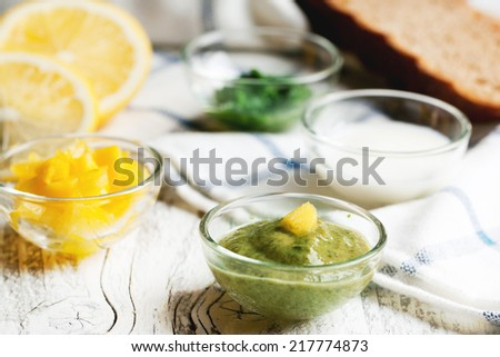 Sauceboats with different sauces and seasonings on white wooden table - stock photo