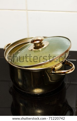 saucepan on electric stove with pasta in boiling water - stock photo