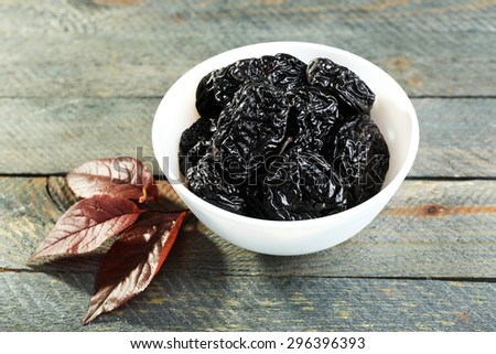 Saucer of prunes with leaves on wooden table, closeup - stock photo