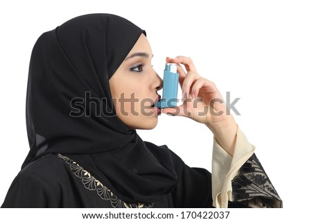 Saudi arabian asthmatic woman breathing from an asthma inhaler isolated on a white background - stock photo