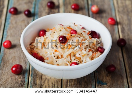Sauerkraut or sour cabbage with cranberries in a white bowl on rustic wooden table, rural style - stock photo