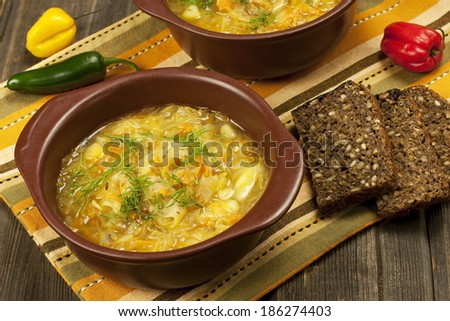 Sauerkraut soup in ceramic  bowl on wooden table - stock photo