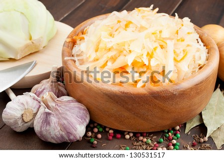 Sauerkraut with carrot in wooden bowl, garlic, spices, cabbage on a cutting board - stock photo