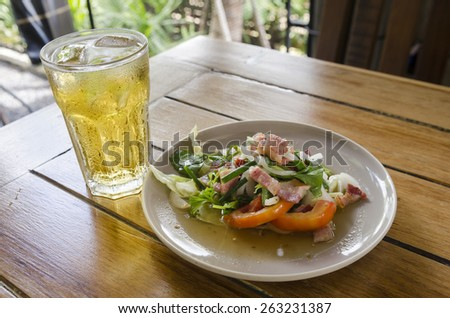 Sausage and green salad plate with tomatoes on white plate and a glass of beer - stock photo