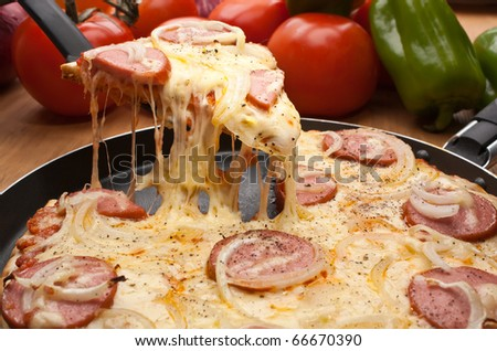 sausage and onion pizza with a slice lifted up - stock photo