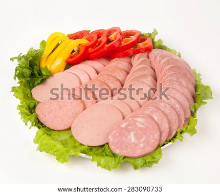 sausage cutting with vegetables and greens on a white plate - stock photo