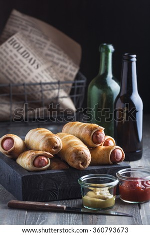 Sausage dough with ketchup, mustard and cold beer served in black wooden box - stock photo