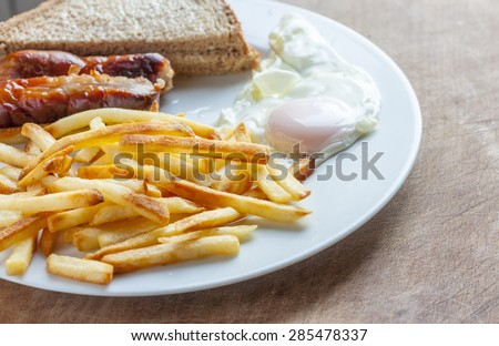 Sausage, egg and chips on a plate - stock photo