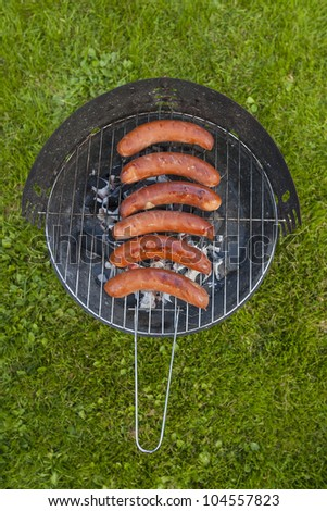 Sausage grilling on a charcoal grill in the garden - stock photo