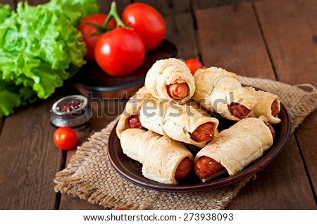 Sausage in the dough sprinkled with sesame seeds on a wooden background in rustic style - stock photo