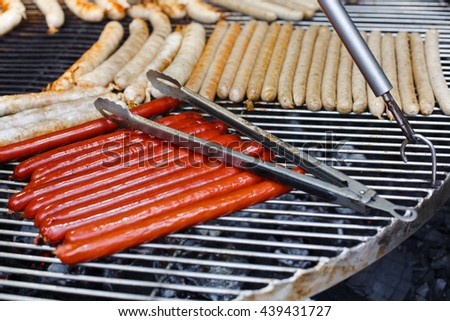 Sausage party. Barbecue large grill outdoors. Cookout bbq food. Big roasted pork and beef german sausages, white polish kielbasa. Meat grilled snack. Street food, fast food. Sausages with metal tongs - stock photo
