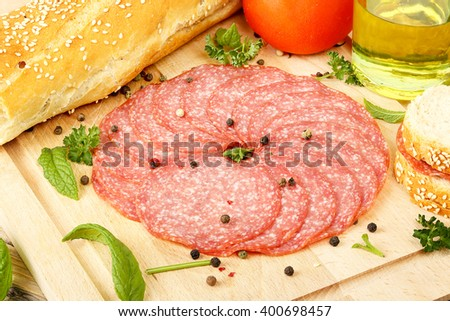 sausage salami slices with other food ingredients on wooden surface - stock photo