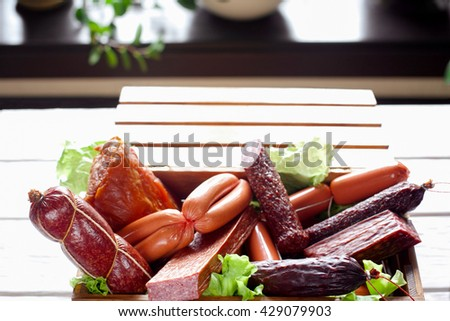 Sausage variety in wooden box. Close-up of delicious sausage assortment in the box. Plenty of sausages decorated with lettuce. - stock photo