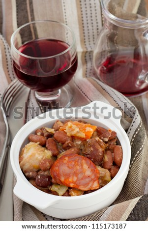 sausages and beans stew with glass of wine - stock photo