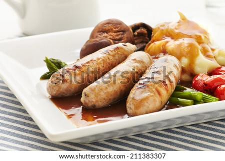 Sausages and Mash in a plate on a blue strip placemat - stock photo