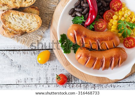 Sausages on the grill with vegetables on a platter. Top view - stock photo