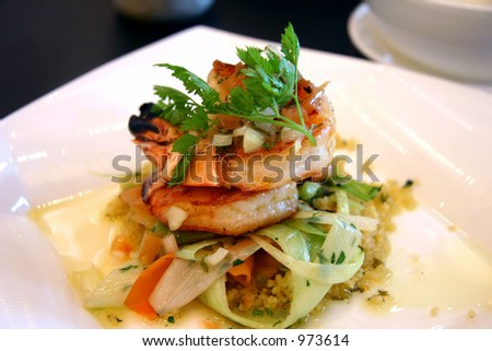 Sauted king prawns with cous cous wrapped in springs of shallots and carrot slices - stock photo