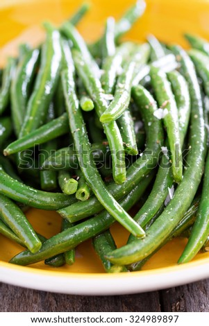 Sauteed green beans with salt and pepper on big plate - stock photo