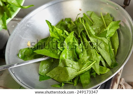 Sauteing or stir frying the japanese spinach in chinese style - stock photo