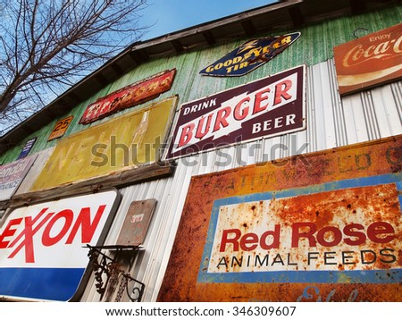 SAVANNAH, GA - FEBRUARY 21, 2015:  A colorful array of vintage advertising signs adorn the outside of an old building at a flea market near Savannah, Georgia, USA.  - stock photo