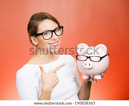 Save money. Closeup portrait happy business woman in glasses, employee, optician, holding piggy bank, pointing with finger isolated red background. Financial concept. Positive face expression, emotion - stock photo