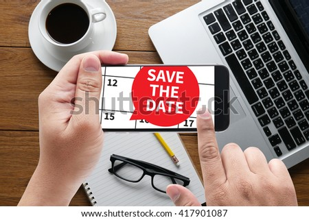 SAVE THE DATE message on hand holding to touch a phone, top view, table computer coffee and book - stock photo