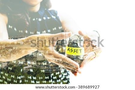 Saving and investment concept image. Double exposure of woman making holding money jar with ASSET label with modern cityscape background. Representing saving for invest in asset. - stock photo