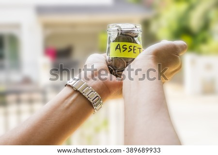 Saving and investment concept image. Hands holding money jar with ASSET label against outdoor background. Representing saving for invest in asset. - stock photo