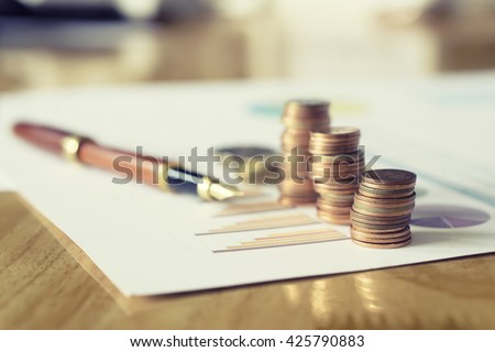 Saving coins money concept,money coins graph,  money stacks of coins ,coins money chart and pen ,copy space.selective focus,vintage color - stock photo