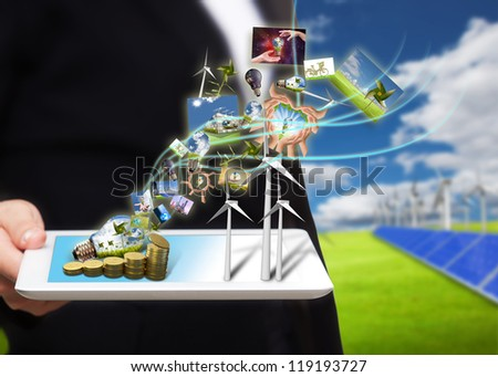 saving energy stream images from tablet pc on the field with solar cell and wind turbine - stock photo