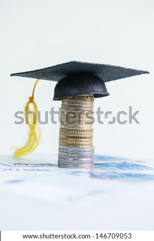 Saving for higher education concept with Mortarboard on top of a stack of Euro coins and 20 Euro banknotes  - stock photo