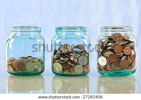 Saving money concept - coins in old jars on reflective surface against blue background - stock photo