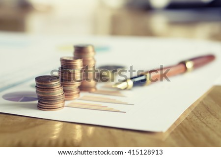 Saving money concept,graph, stacks of coins ,chart and pen ,copy space.selective focus,vintage color - stock photo