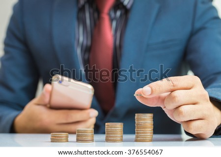 Saving money concept,Investment,Business man hand putting money coin stack growing business - stock photo