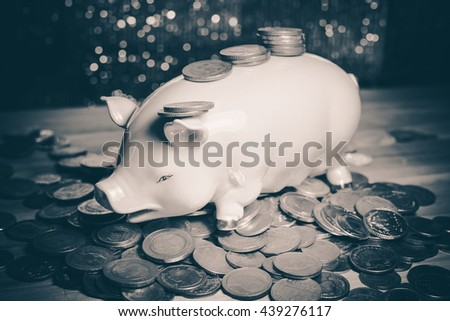 Saving money concept, Many coin and Piggy Bank. Save money with stack money coin for growing your business. Piggy bank on a pile of coins. - Dark and Vintage tone. - stock photo