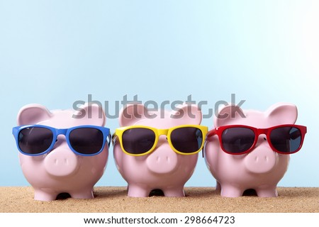 Saving money for vacation.  Row of three piggy banks on beach with sunglasses.  Travel concept.  Copy space. - stock photo