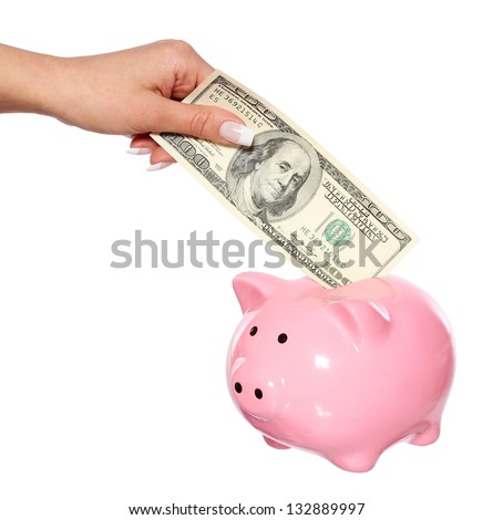 saving money, hand is putting money into piggy bank isolated on white - stock photo