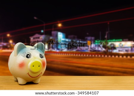 saving money in piggy bank on wooden ground over blurred image of car moving in crowded night city street in Thailand,saving money for healthcare future illness concept - stock photo