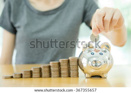 saving money-young woman putting a coin into a money-box-close up - stock photo