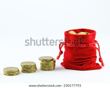 saving up gold coins in red bag  - stock photo