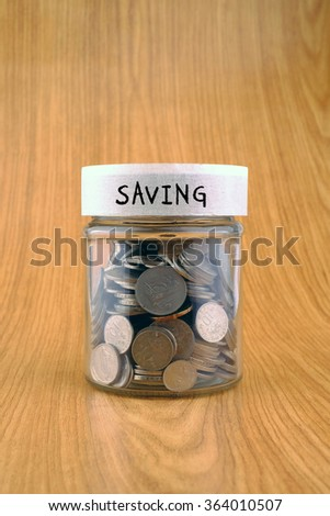 savings concept, coins in jar with saving label on wooden background. - stock photo