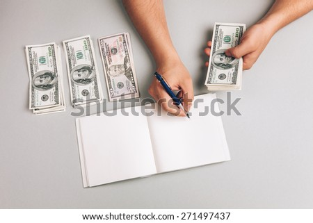 savings, finances, economy and concept - close up of man counting money and making notes - stock photo