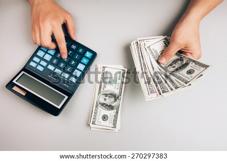savings, finances, economy and concept - close up of man with calculator counting money - stock photo